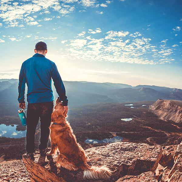 Man and dog on top of a cliff looking at the view